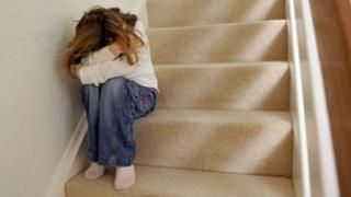 Girl sitting on staircase, covering her face