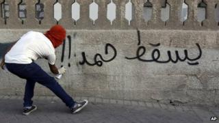 "A man spray-paints ""Down with Hamad!!"" on a wall Daih, Bahrain (28 September 2012)"
