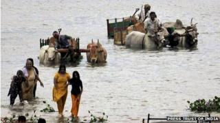 A family crosses a lake to take shelter in a safer place as cyclone Nilam threatens to hit Nellore district of Andhra Pradesh.