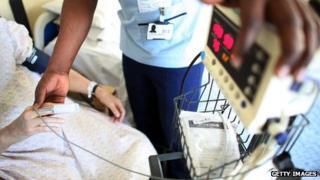 A nurse takes a patients temperature