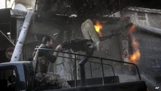 A rebel fighter fires a gun towards government forces in Aleppo, Syria (4 November 2012)