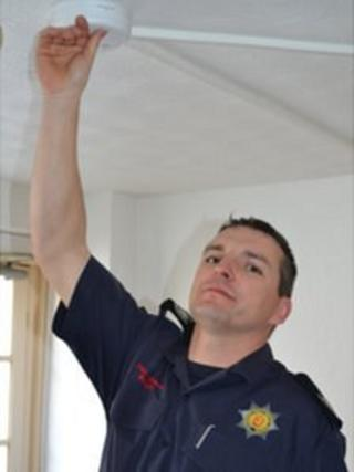 Guernsey Fire Safety Officer Pierre Laine testing a fire alarm