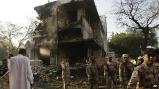 Troops of Pakistan's para-military force stand near the site of an explosion in Karachi, Pakistan on Thursday, Nov. 8, 2012.