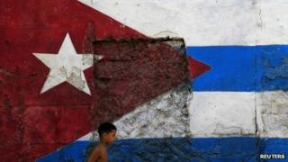 Child walks past a Cuban flag painted on wall in Havana