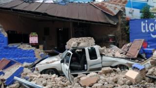 Car in ruins of collapsed house
