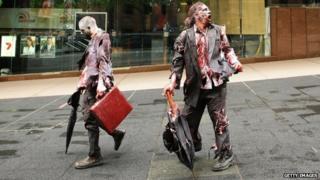 Two men dressed as zombie business men walk down a street