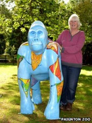 "Devon artist Sue Misselbrook with ""Herbert"" gorilla, featuring flags with African designs"
