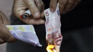 Protestor in Athens burns euro note