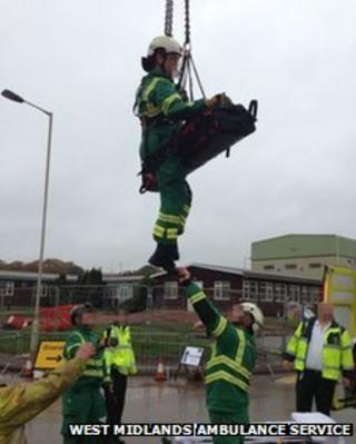 Ambulance staff and patient suspended by crane