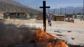 Tyres burn after being set alight and placed on a road sign north of Cape Town during a farm workers strike - 14 November 2012