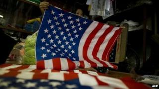 A woman folding flags of the US at a shop in Rangoon, 16 November 2012