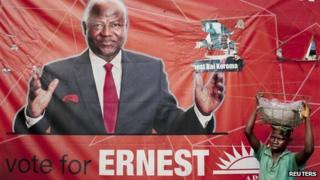 Fruit vendor in front of a campaign poster for incumbent President Ernest Bai Koroma, in Freetown, Sierra Leone