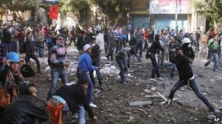 Egyptian protesters throw stones at Egyptian riot police, unseen, in Tahrir Square in Cairo, Egypt, Monday, 21 Nov 2011