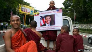 Burmese monks hold a poster showing US President Barack Obama during his arrival at Yangon International airport 19 November 2012