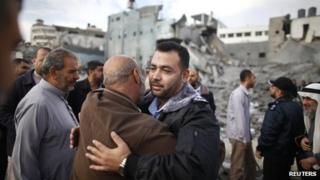A Hamas police officer is hugged by a Palestinian man after they returned to their destroyed police headquarters in Gaza City