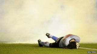 Goalkeeper Juan Carlos Olave from Argentine soccer club Belgrano lies on the pitch after being hit by a flare in a match against Independiente