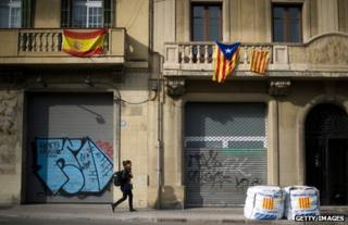 A Spanish flag (left) hangs beside Catalan flags on a Barcelona street, 22 November