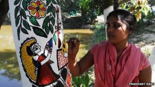 A Madhubani artist painting the traditional art form on a tree trunk