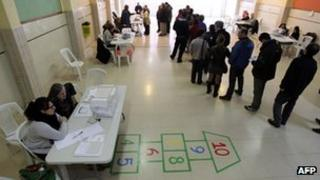 People queue to cast their ballots at a polling station in Barcelona.