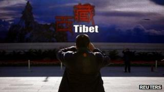 A man taking a photograph in front of a screen displaying propaganda about China's Tibet Autonomous Region in Beijing, 12 November 2012