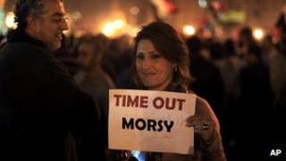 A protester holds a placard against the Egyptian president at an opposition rally in Tahrir Square in Cairo, Egypt, Tuesday, Nov. 27,