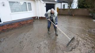 Tom Wynne sweeps muddy sediment off the drive of a home after flood waters receded in St Asaph