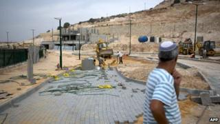 An Israeli settler observes Palestinian labourers working on the expansion of the Jewish settlement of Tzufim near the West Bank town of Qalqilya