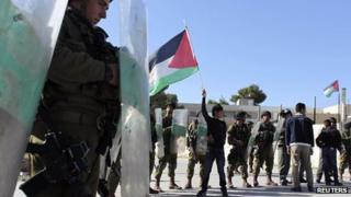 Palestinian youth waves a flag in front of Israeli soldiers (29 November 2012)