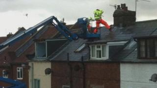 Contractors on the roof of the row of houses in Whitby