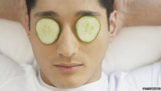 Man using cucumbers on eyes