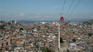 Cable cars travel above the Complexo do Alemao shanty town in Rio de Janeiro