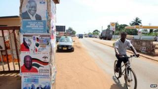 Man in Ghana cycles past presidential election posters featuring President John Dramani Mahama and his main challenger, Nana Addo Dankwa Akufo-Addo, on 23 October 2012