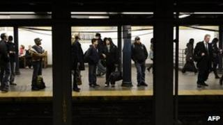 Commuters wait at the 59th Street subway station in this 1 November 2012 file photo in New York