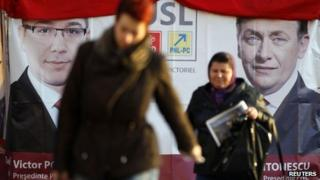 """People walk past an election poster with the pictures of Romania""""s Social Liberal Union (USL) leaders, leftist Prime Minister Victor Ponta, the president of Social Democrat Party, and Crin Antonescu, the president of National Liberal Party (R), in downtown Bucharest December 4, 2012."""