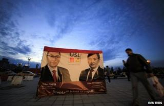 People walk past election posters in Bucharest, 3 December