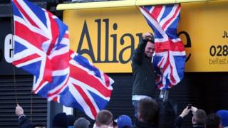 Loyalists erect flags on Alliance Party offices