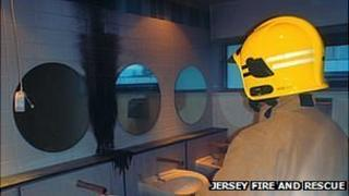 Jersey firefighter inspects damage caused by fire in toilets at Grainville School
