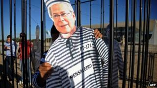 Image of convicted politician Jose Dirceu wearing prison clothes is held by a protester outside the Supreme Court headquarters in Brasilia, Brazil, on 3/8/12