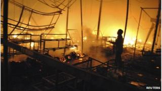 Flames engulf market stalls in Siem Reap as a man watches the blaze