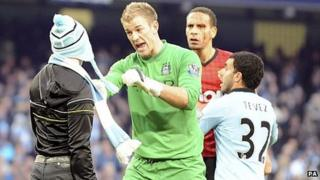 Manchester City's Joe Hart stops a fan who walked onto the pitch to confront Manchester United's Rio Ferdinand