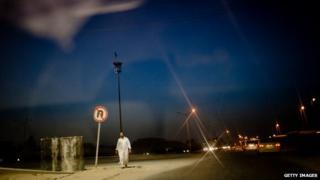 A man walking on the street at night in Misrata, Libya