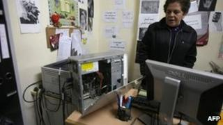 A woman looks at a computer with a missing hard-drive inside the offices of Addameer in Ramallah (11 December 2012)