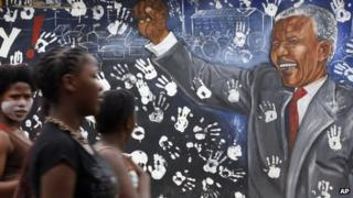 Young women walk by a mural depicting former South African President Nelson Mandela at Alexandra township in Johannesburg, South Africa, on Tuesday 11 December 2012