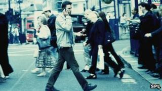 Man on mobile phone crossing road
