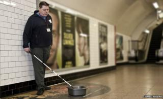 Mark Campbell busking with his cane and washing up bowl