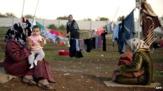 Mothers and children sit in a refugee camp near the Syrian city of Azaz (5 December 2012)