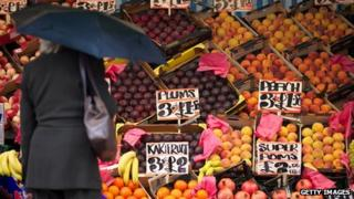 Woman surveys fruit for sale at a market