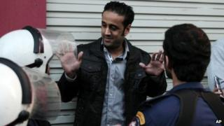 Sayed Yousif al-Muhafdha is confronted by security forces personnel in Manama (17 December 2012)