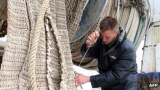 French fisherman mending nets