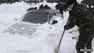 Emergency workers dig out a car trapped in snow in western Ukraine. Photo: December 2012